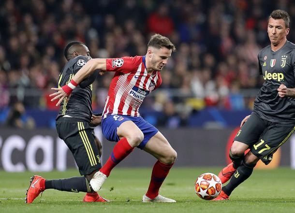 Saúl protege el esférico ante la mirada de Mandzukic, que volvía para enfrentarse a sus ex-compañeros. Foto: Web oficial Club Atlético de Madrid