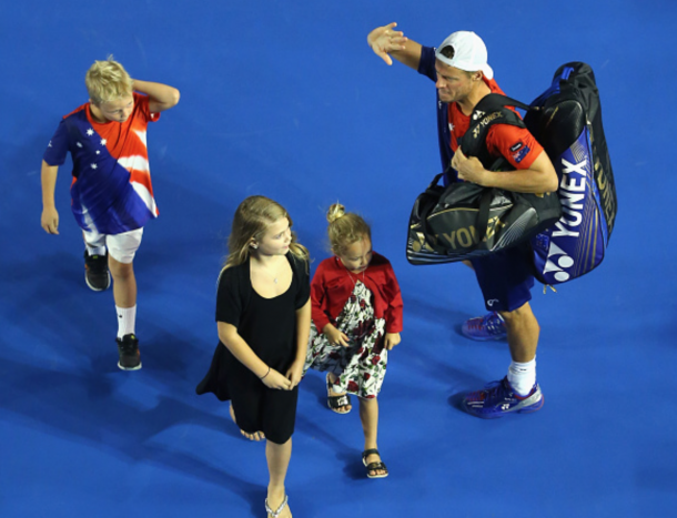 Hewitt waves goodbye to the Rod Laver Arena fans one last time as he walks off with his three kids. Quinn Rooney/Getty Images
