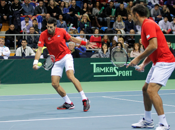 Novak Djokovic (L) and Nenad Zimonjic of Serbia in action against Marin Draganja and Franko Skugor of Croatia during their men's double match on the day two of the Davis Cup match between Serbia and Croatia on March 07, 2015 in Kraljevo, Serbia. (Photo by Srdjan Stevanovic/Getty Images)