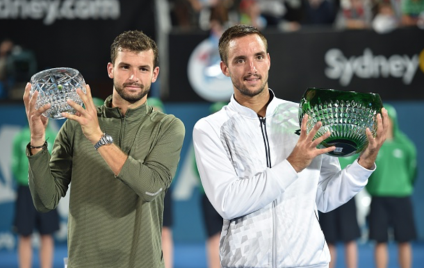 Viktor Trioicki of Serbia (R) holds the winners trophy after beating Grigor Dimitrov of Bulgaria (L) 2-6, 6-1, 7-6 (9-7) in the men's singles final match at the Sydney International tennis tournament in Sydney on January 16, 2016. AFP PHOTO / Peter PARKS