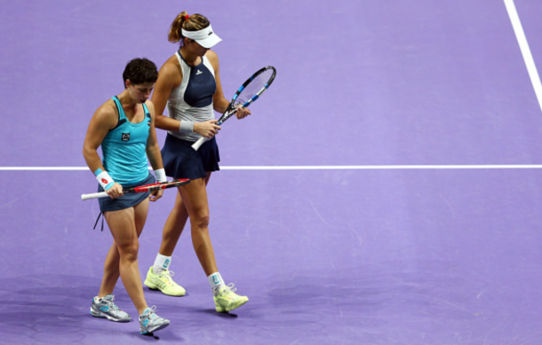 Carla Suarez Navarro and Garbine Muguruza of Spain speak on court during their doubles final match against Martina Hingis of Switzerland and Sania Mirza of India during the BNP Paribas WTA Finals at Singapore Sports Hub on November 1, 2015 in Singapore. (Photo by Clive Brunskill/Getty Images)