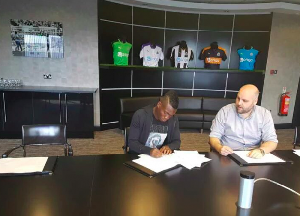 Atsu signing the paperwork needed to complete his loan spell to Newcastle (Photo: Twitter)