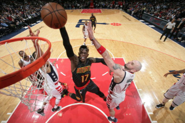 Schroder rises up for the dunk over several Wizards defenders. (Photo by Ned Dishpan/Getty Images)