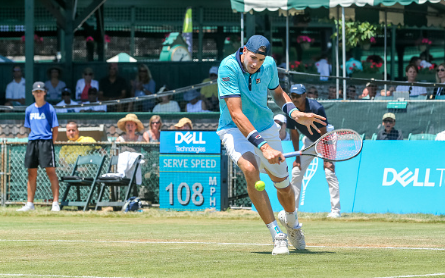 John Isner hits a slice return to Novikov