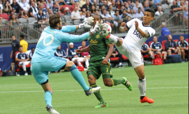 Fredy Montero (right) goes after a loose ball with Timbers goalkeeper Jake Gleeson | (Photo: John May - MLSGB)