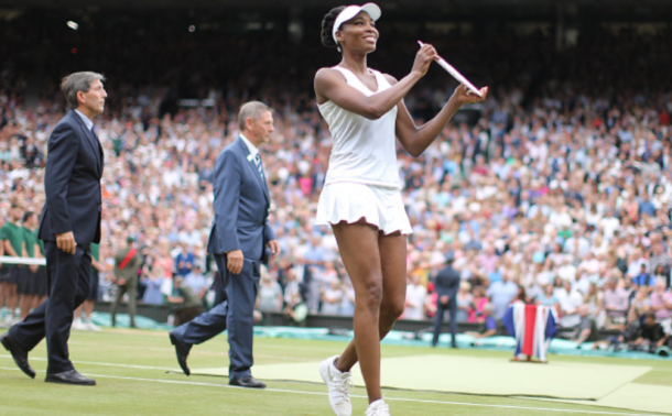 Venus Williams shows off her runner-up trophy after the Wimbledon final (Tim Clayton/Corbis/Getty Images)