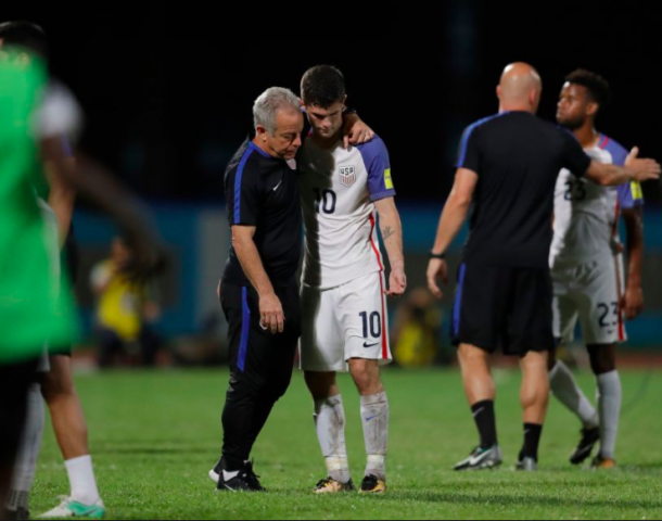 Christian Pulisic is comforted by coaches after the USMNT lost 2-1 to Trinidad and Tobago. | Photo: Rebecca Blackwell | AP