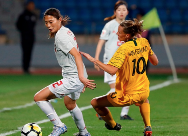 Seattle Reign FC and Japan defender Rumi Utsugi (Left) keeps the ball away from Orlando Pride and Australian midfielder Emily van Egmond. (Photo by JACK GUEZ/AFP/Getty Images)