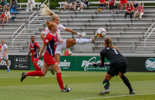 Rachel Daly (White) reaches out to touch the ball past Tori Huster (Red) and Spirit goalkeeper Aubrey Bledsoe (Black) (Photo: Kelley Piper @kpiperphotos)