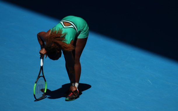 Serena checking out her ankle which she rolled before being broken in the seventh game (Cameron Spencer/Getty Images)
