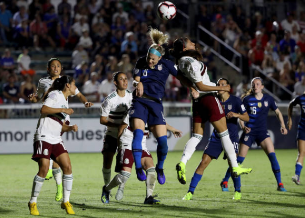 Julie Ertz (center) wins a header while surrounded by Mexican players. | Photo: Streeter Lecka - Getty Images