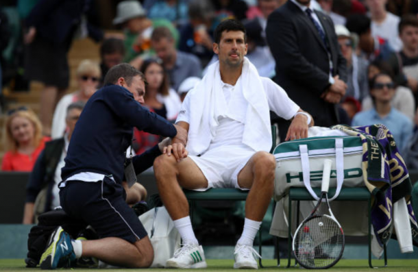 Novak Djokovic getting treated for his elbow (Photo: Julian Finney/Getty Images)