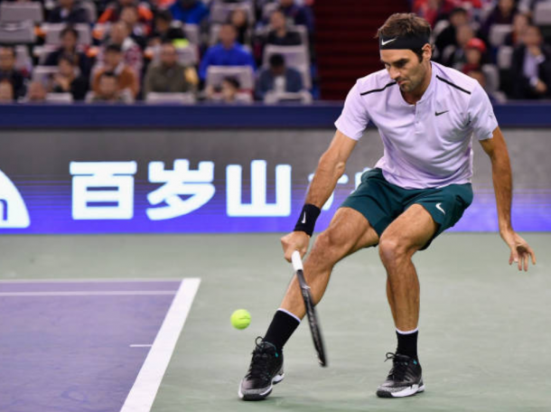Roger Federer reaches down low for a return shot (Photo: Lintao Zhang/Getty Images)