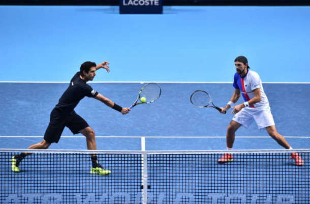 Marcelo Melo plays a volley with Lukasz Kubot looking on (Photo: Glyn Kirk/Getty Images)