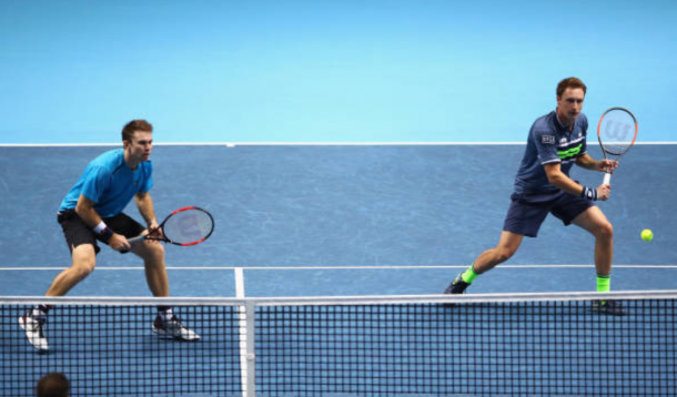 Henri Kontinen strikes a return shot with John Peers ready to react (Photo: Clive Brunskill/Getty Images)