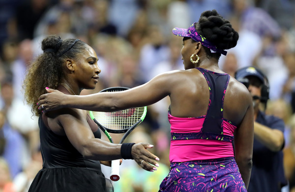 Serena and Venus meet at the net for a warm embrace after the quick encounter | Photo: Elsa/Getty Images North America