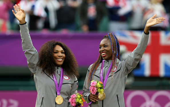 Serena and Venus Williams wave to the crowd after receiving their gold medals during the women's doubles prize ceremony at the 2012 London Olympics.