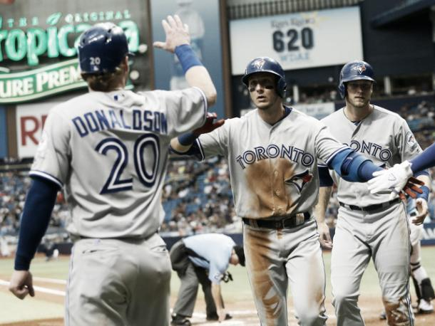 Josh Donaldson greets Troy Tulowitzki at home plate after he rounds on the bases. (Brian Blanco/Getty Images)