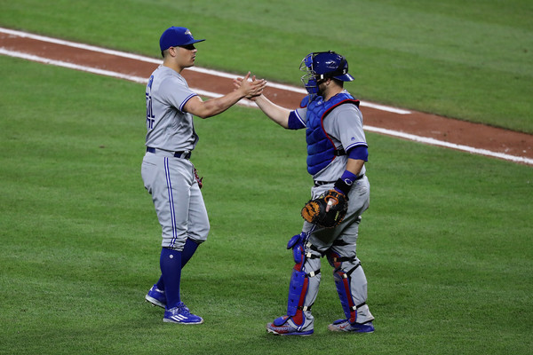 Closing pitcher Roberto Osuna and catcher Miguel Montero celebrate after the game. | Photo: Rob Carr/Getty Images