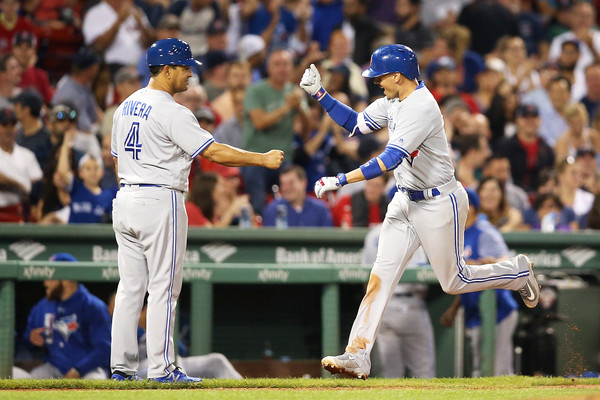 Ryan Goins celebrates with third base coach Luis Rivera after hitting a solo home run in the ninth to give Toronto some insurance against the Red Sox. | Photo: Adam Glanzman/Getty Images