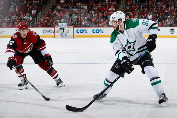 Tyler Seguin #91 of the Dallas Stars skates with the puck under pressure from Tyler Gaudet #32 of the Arizona Coyotes during the second period of the NHL game at Gila River Arena on February 18, 2016 in Glendale, Arizona. The Coyotes defeated the Stars 6-3. (Feb. 17, 2016 - Source: Christian Petersen/Getty Images North America)