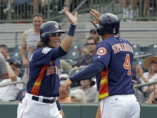 Houston Astros' Colby Rasmus, left, high-fives teammate George Springer (4) as they celebrate Rasmus' home run in the first inning in a spring training baseball game. (Photo: John Raoux, Associated Press)
