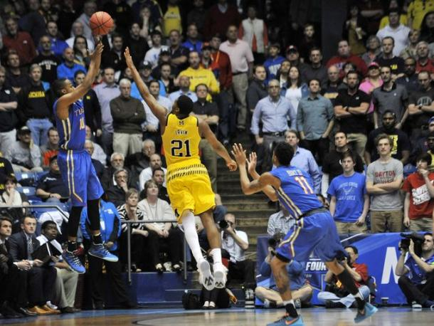Michigan guard Zak Irvin (21) defends a 3-point attempt by Tulsa guard James Woodard (10) in the last minute of the game.  (Robin Buckson, Detroit News)