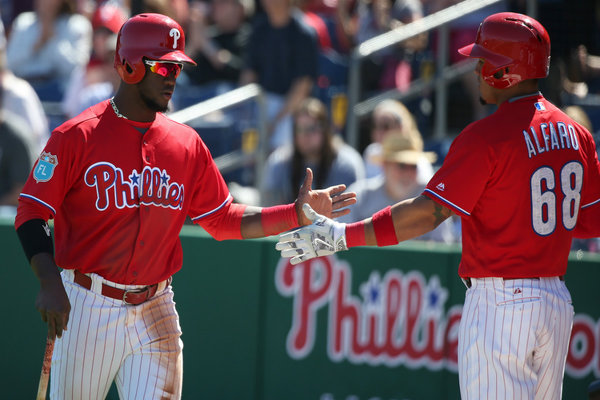 Phillies' Odubel Herrera, left, celebrates with teammate Jorge Alfaro, right, after he scores in the 1st inning as the Phillies play the University of Tampa. (DAVID MAIALETTI)