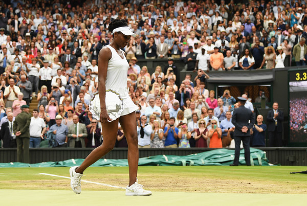 Venus Williams walks off the famous Wimbledon Centre Court with her runner-up trophy, looking dejected | Photo: David Ramos/Getty Images Europe