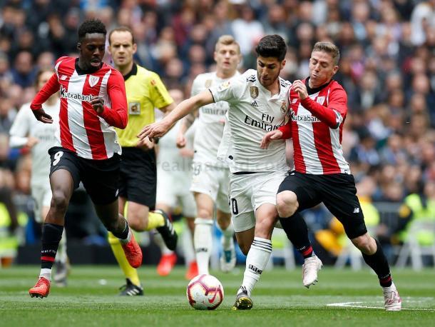 Asensio en una carrera trata de ser frenado / Foto: Real Madrid