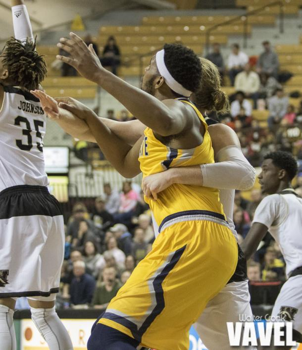 Drake LaMont (42) of Western Michigan fights for position under the basket with Adonis De La Rosa (1) of Kent State. Photo: Walter Cronk