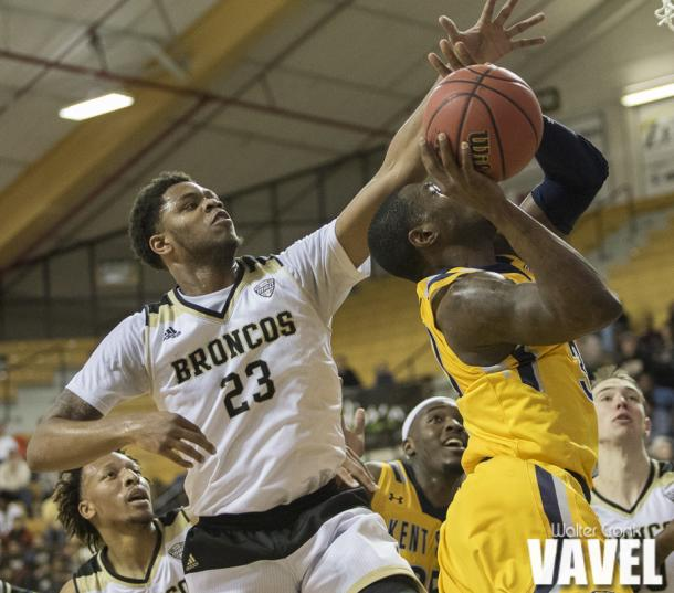Reggie Jones (23) gets called for the foul while trying to block the shot of Deon Edwin (30). Photo: Walter Cronk