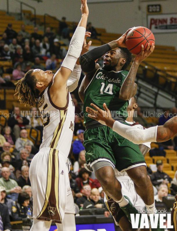 Fred Sims Jr. (14) attempting the shot near the baasket over Brandon Johnson (35). Photo: Walter Cronk