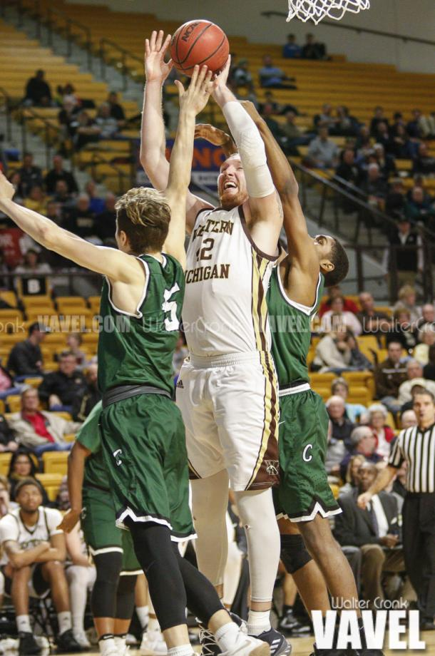 Drake LaMont (42) go's for two points under the basket in between two defenders. Photo: Walter Cronk