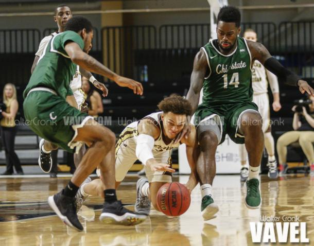Bryce Moore (0) hustles after the loose ball in between two Chicago State defenders. Photo: Walter Cronk