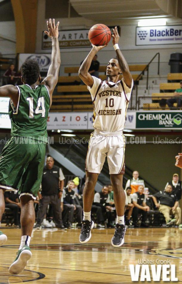 Thomas Wilder (10) attempts the three pointer while Fred Sims Jr (14) closes in. Photo: Walter Cronk