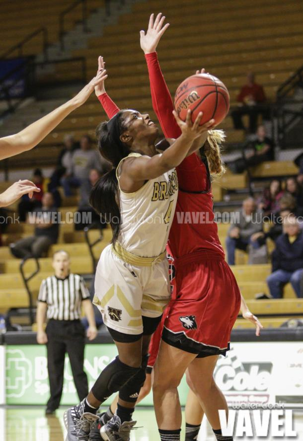 Deja Wimby (4) attempts the shot around Kelly Smith (25). Photo: Walter Cronk