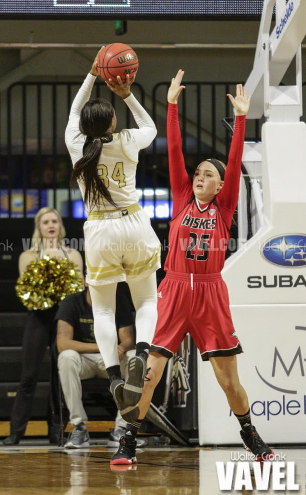 Jasmyn Walker (34) attempts the three pointer over Kelly Smith (25). Photo: Walter Cronk