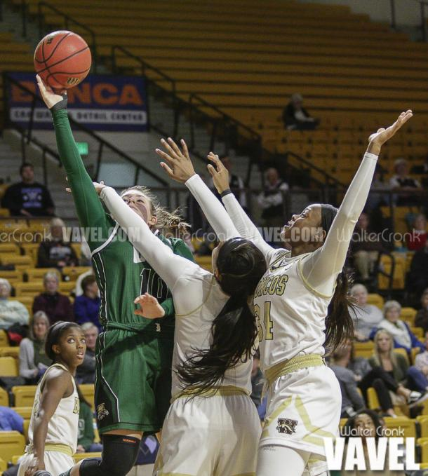 Dominique Doseck (10) to the hoop past two defenders. Photo: Walter Cronk