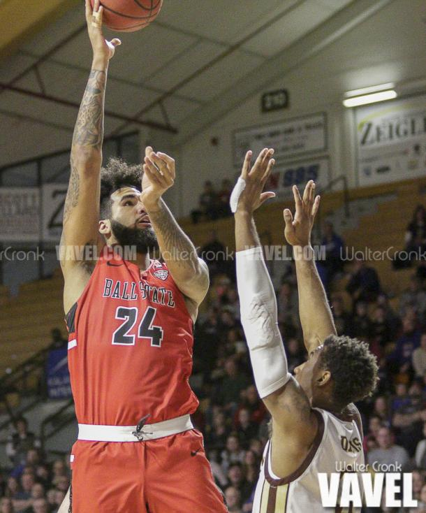Trey Moses (24) takes the one handed shot over Josh Davis (3). Photo: Walter Cronk