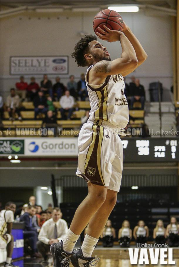 Michael Flowers (1) shoots for three points. Photo: Walter Cronk