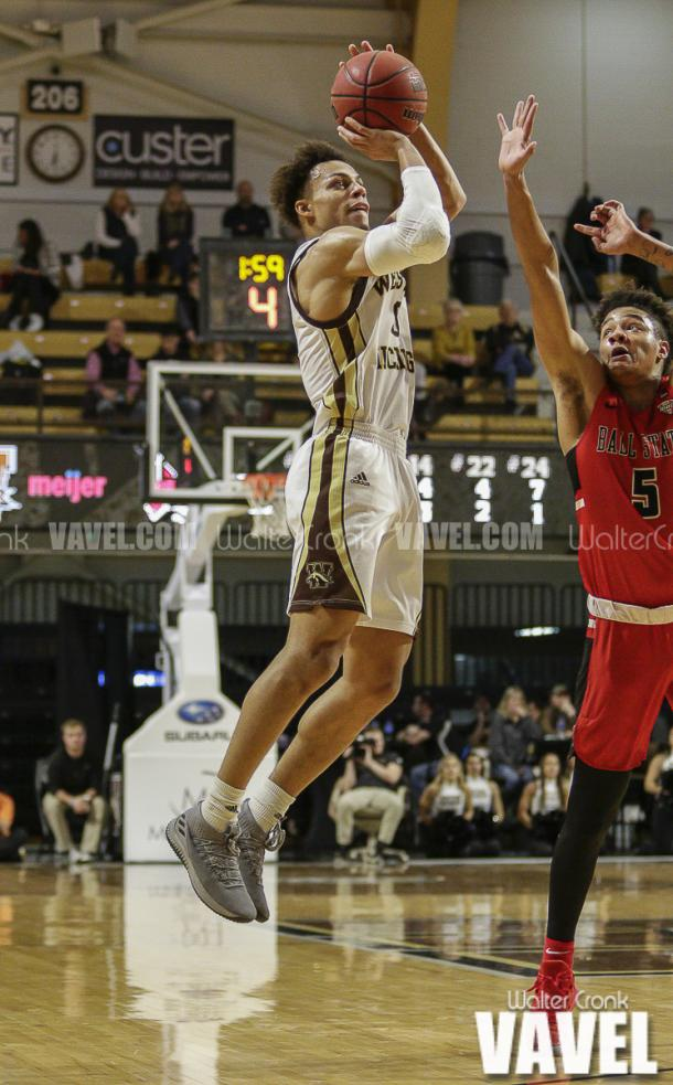 Bryce Moore (0) attempts the three point shot. Photo: Walter Cronk