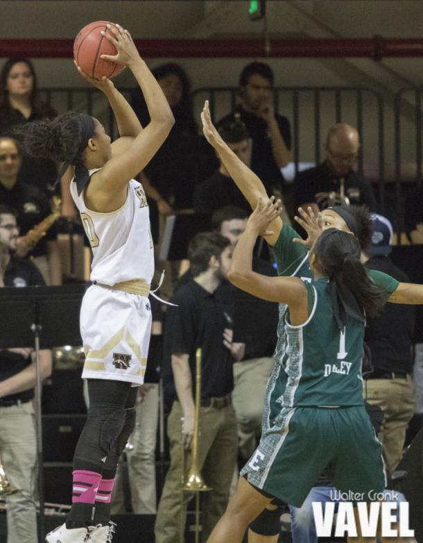 Breanna Mobley (10) takes the jump shot over two Eastern Michigan defenders. Photo: Walter Cronk