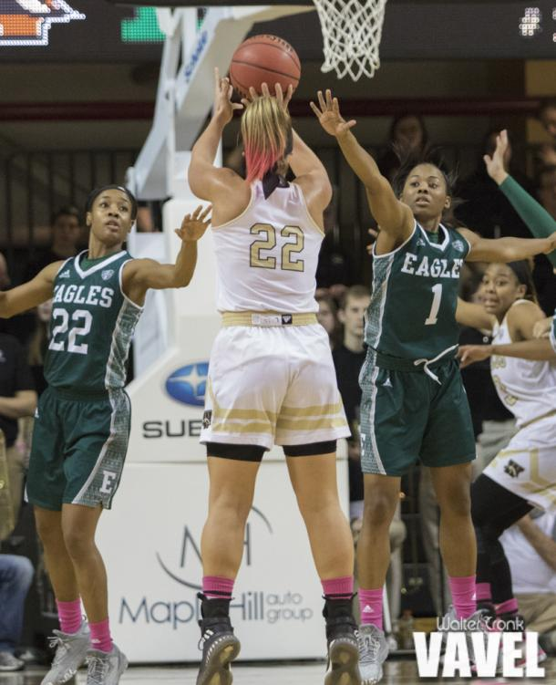 Meredith Miller (22) takes the shot over Sheyna Deans (22) and Sasha Dailey (1). Photo: Walter Cronk