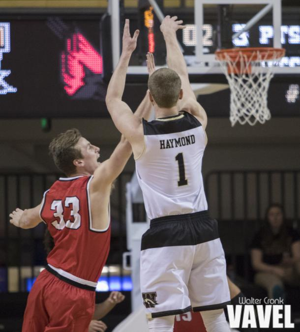 Tucker Haymond (1) takes the three point shot with Ryan Weber (33) in his face. Photo: Walter Cronk