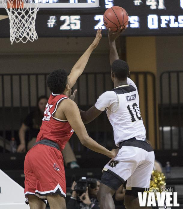 Thomas Wilder (10) takes the one handed shot around Tahjai Teague (25). Photo: Walter Cronk