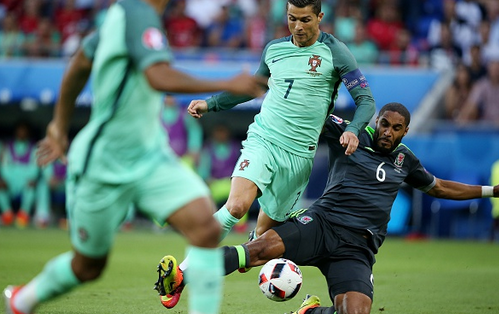 Williams (far left) performing a clean slide tackle to dispossess Real Madrid forward Cristiano Ronaldo during Wales' semi-final defeat against Portugal in the Euros. | Photo: Getty