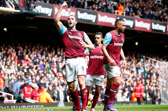Carroll celebrates his side's second goal, whilst Arsenal fans are stunned into silence after a promising first 45. | Photo: Getty