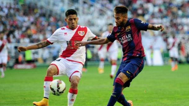 En la imagen, Aquino y Neymar disputándose la pelota en el campo.