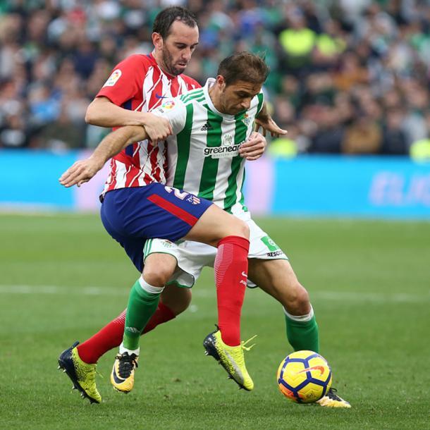 Juan Fran y Joaquín pugnan por un balón, en el encuentro frente al Betis. Fuente: atleticodemadrid.com